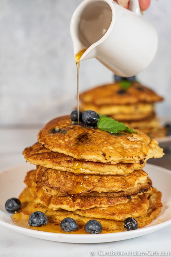 pouring maple syrup on Fluffy Keto Blueberry Pancakes Recipe