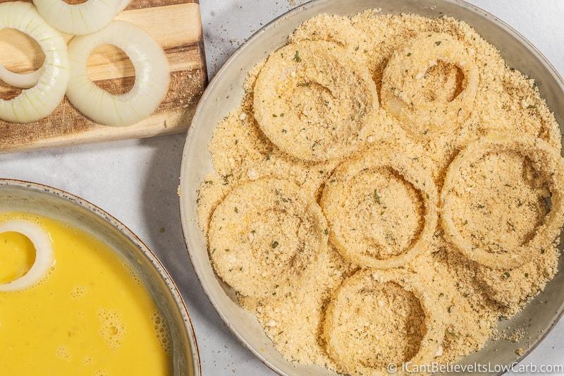 coating Keto Onion Rings in almond flour breadcrumbs