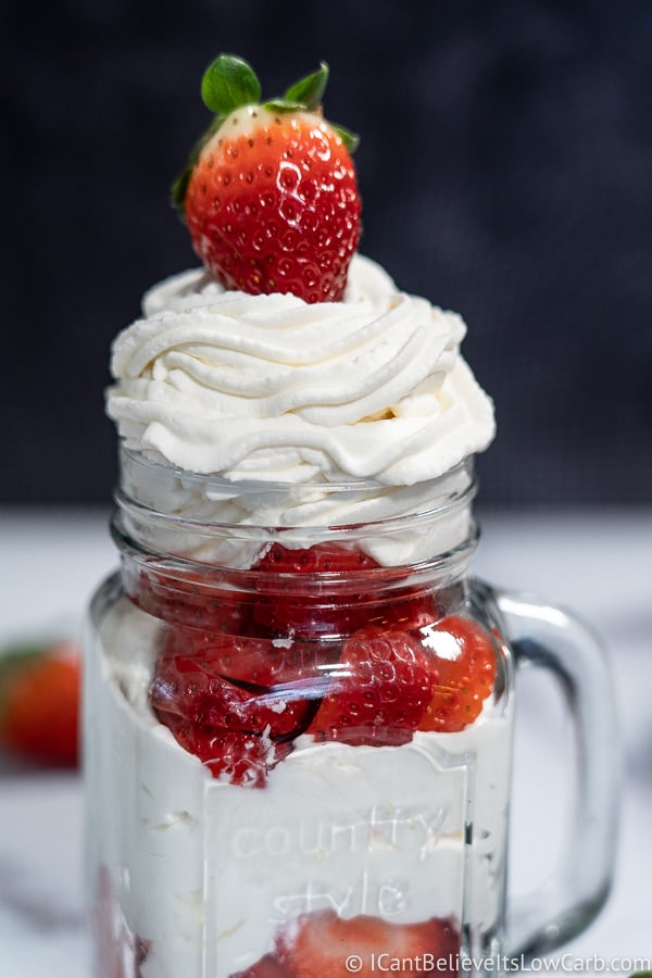 Jar of Keto Sugar-Free Whipped Cream with a strawberry on top