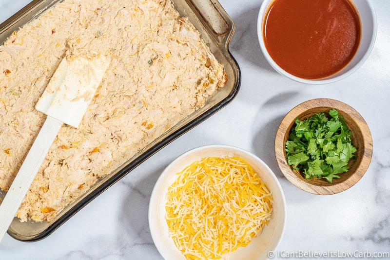 putting low carb Chicken Enchilada Casserole in baking dish