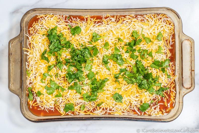 putting Keto Chicken Enchilada Casserole in oven