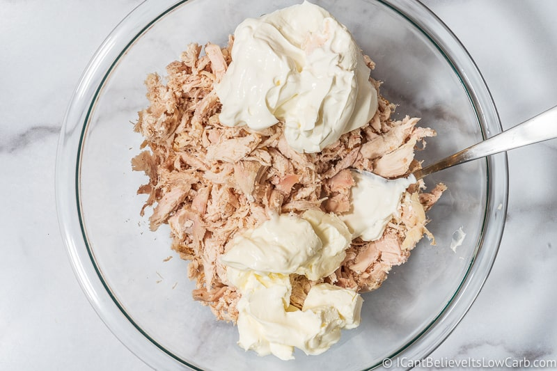 mixing chicken for Keto Chicken Enchilada Casserole