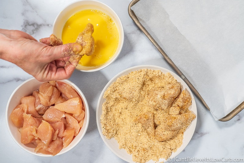 Keto Chicken Nuggets dipping in almond flour