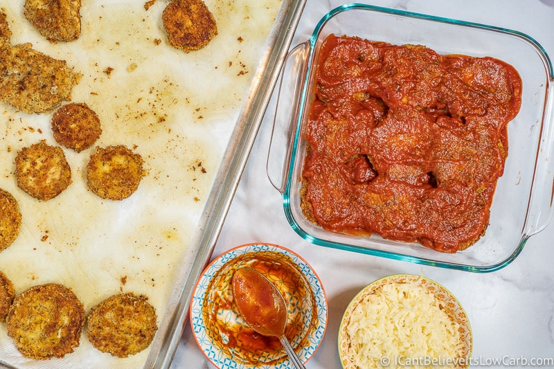 Keto Eggplant Parmesan covered in tomato sauce in baking dish