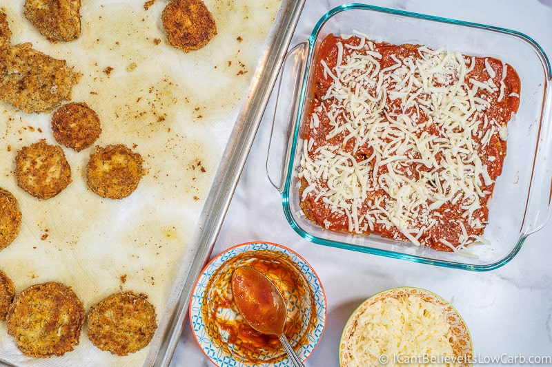 assembling Keto Eggplant Parmesan in baking dish with cheese