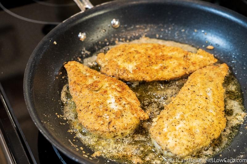 Keto Chicken Parmesan frying in a pan