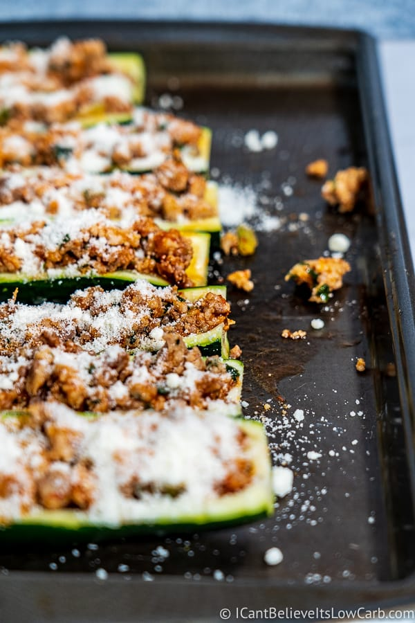adding parmesan cheese to Low Carb Zucchini Boats