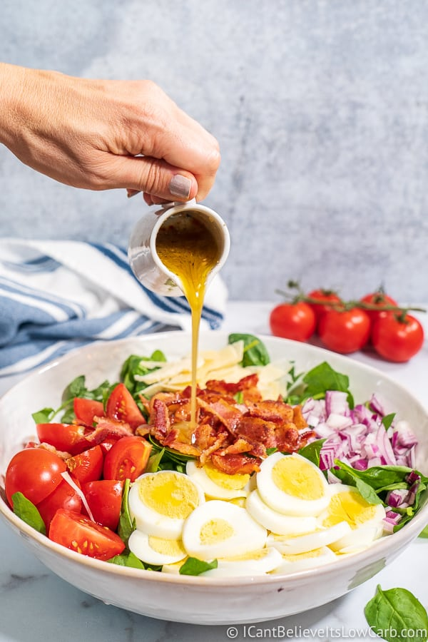 pouring dressing over a Spinach Salad with egg