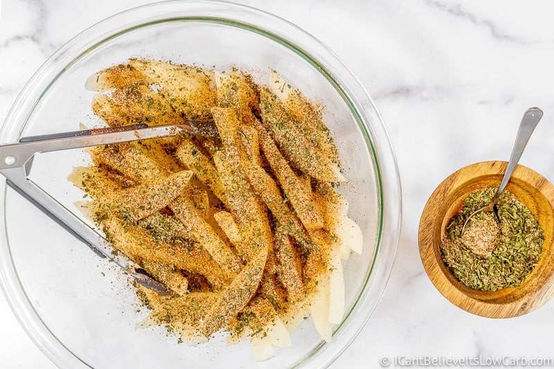 covering Keto Jicama Fries with spices