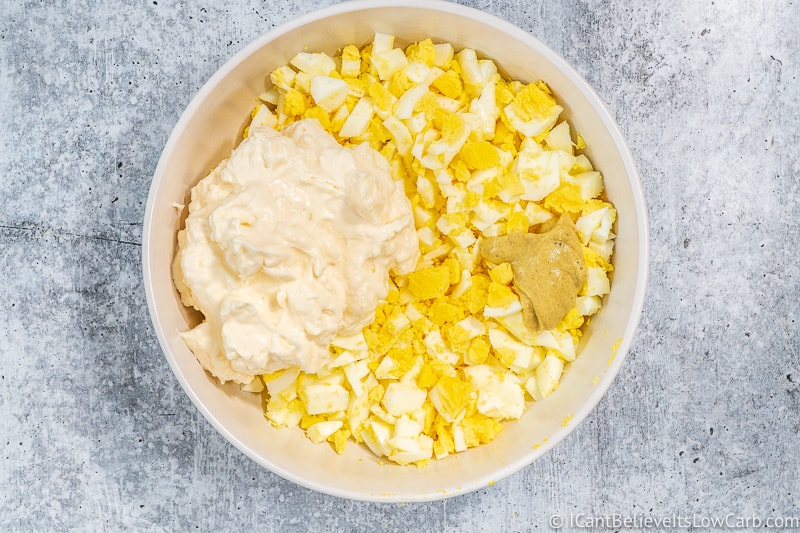 mayo and mustard in a bowl of chopped eggs