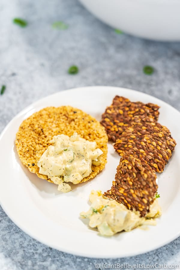 scooping Keto Egg Salad on crackers