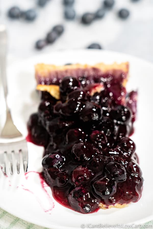 Sugar Free Blueberry Pie recipe with fresh blueberries on white plate