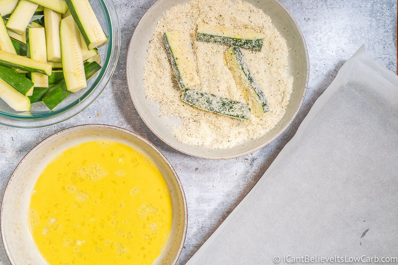 coating Zucchini Fries with parmesan cheese and spices