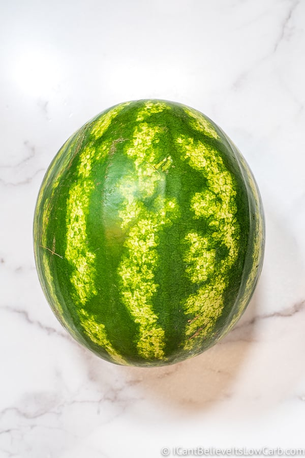 a big round watermelon on white marble