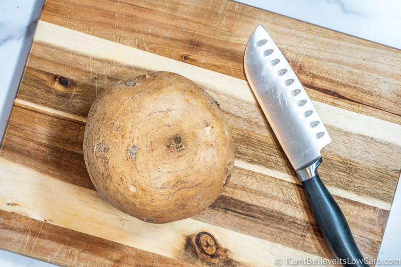 raw jicama on cutting board with knife