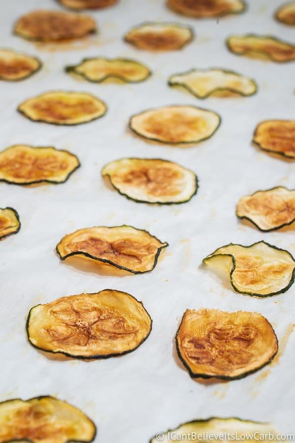 zucchini chips laying on a baking sheet