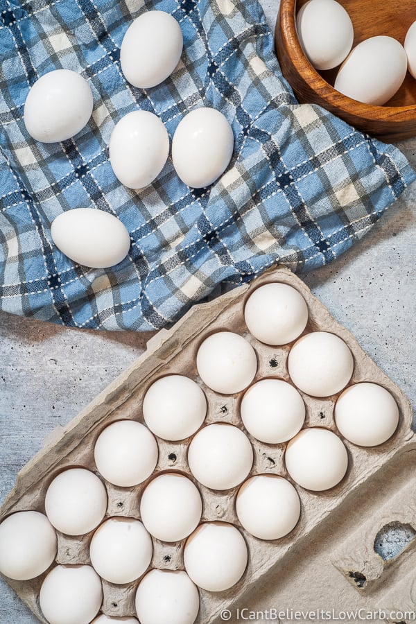 Raw Eggs in a carton and on blue towel