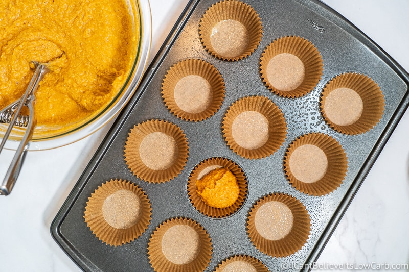 filling Muffin liners with low carb pumpkin muffin mixture