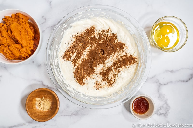 adding spices to pumpkin cheesecake filling