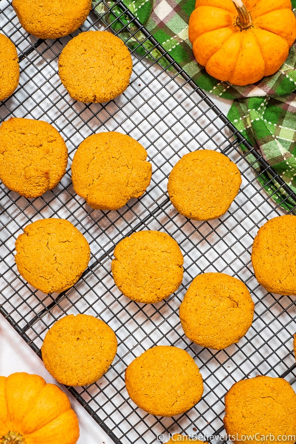 Keto Pumpkin Cookies cooling on a rack with pumpkins