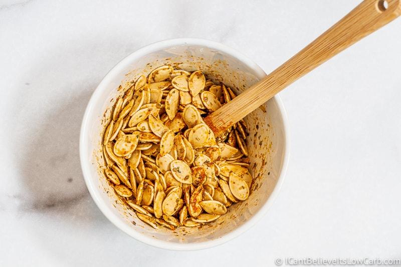 mixing seasonings on Pumpkin Seeds