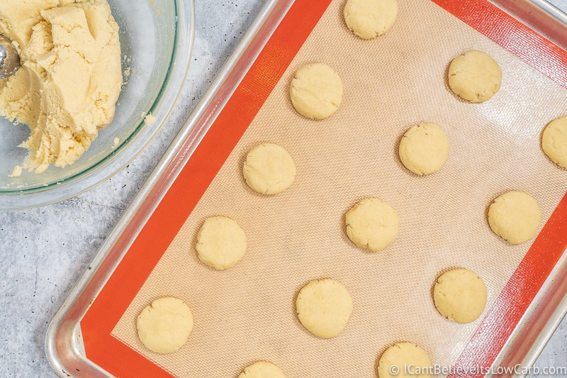 Pressing Cream Cheese Cookies on tray