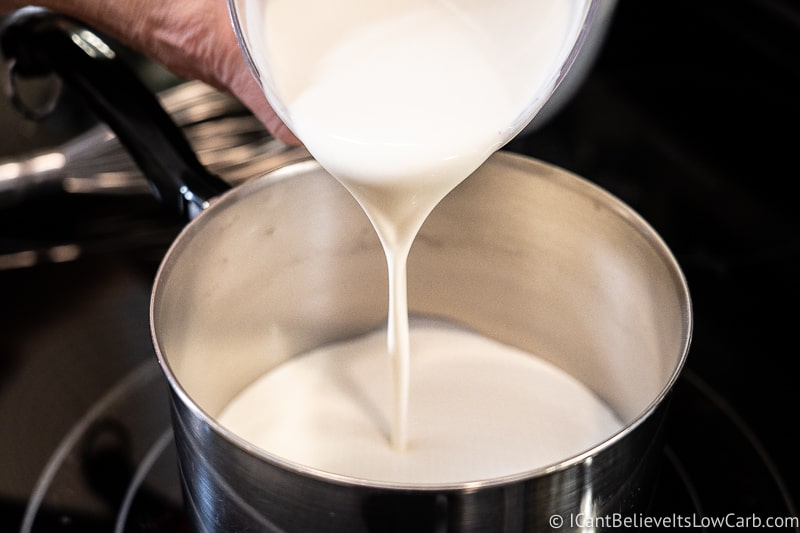 pouring heavy cream into the pot