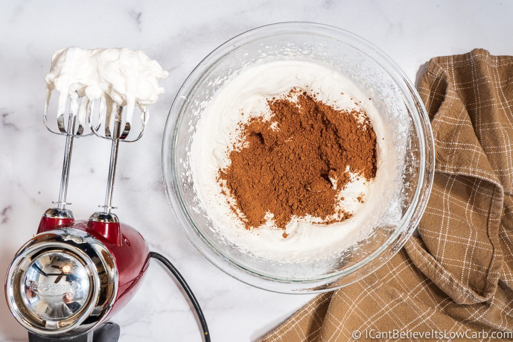 adding cocao powder to whipped cream