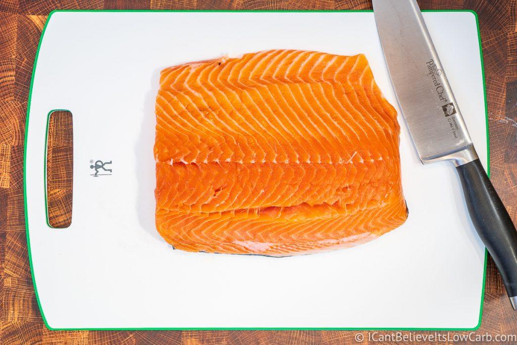 fresh salmon on cutting board with knife