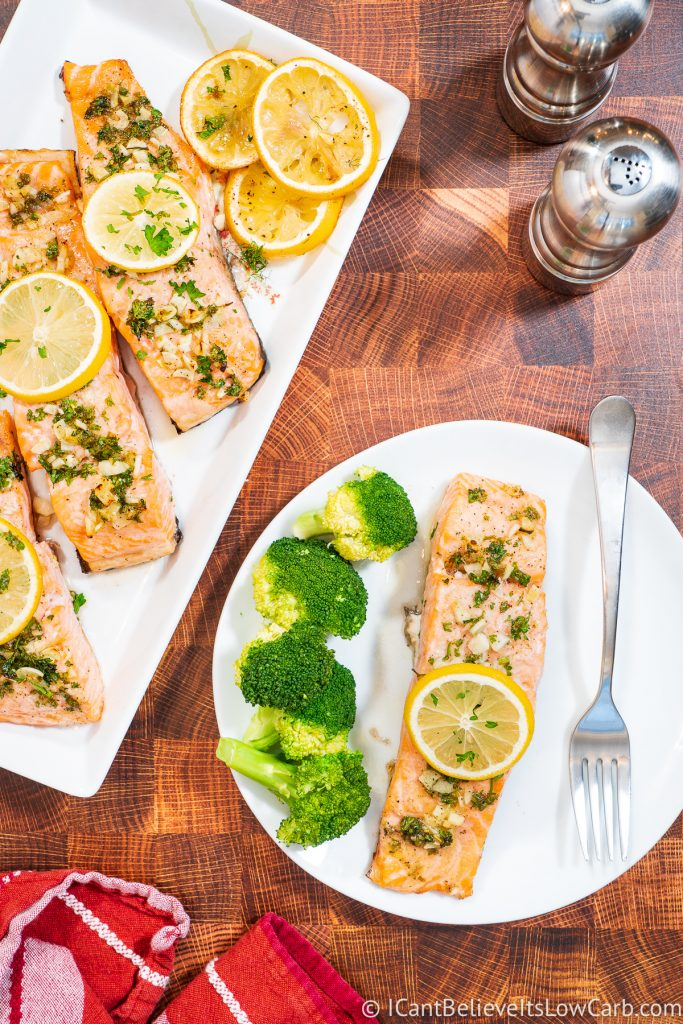 Tray full of Baked Salmon and one filet on a plate