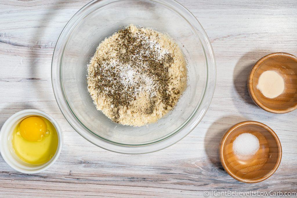 adding Italian seasoning to crust mixture