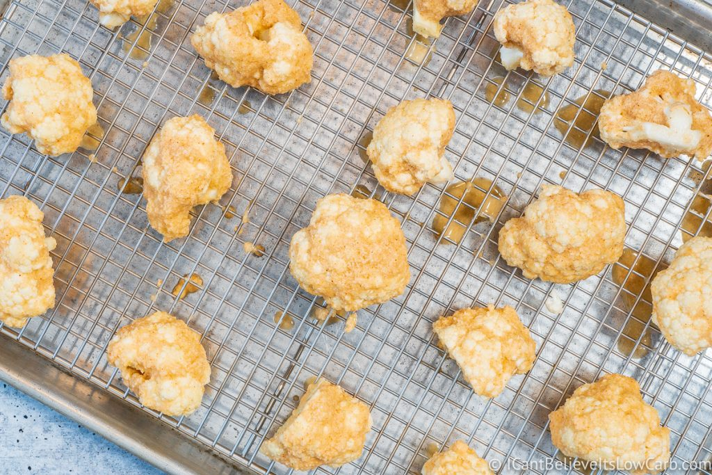 Buffalo Cauliflower bites on baking sheet before going in the oven