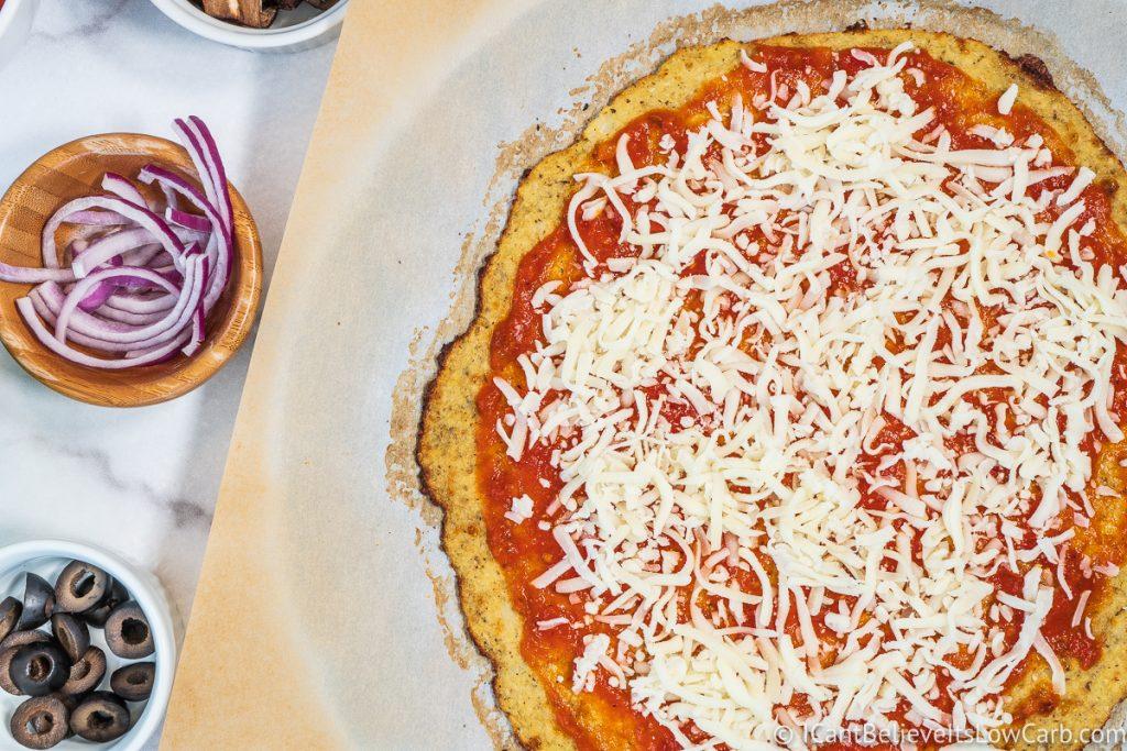 Adding mozzarella cheese to Cauliflower Pizza
