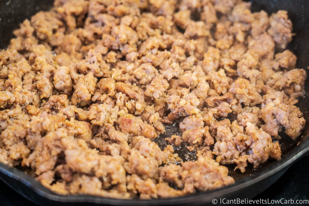 spicy sausage frying in cast iron pan