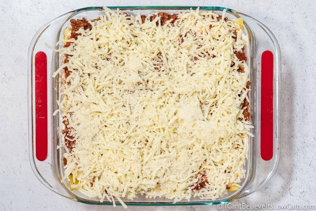 adding final layer of cheese on top of the lasagna