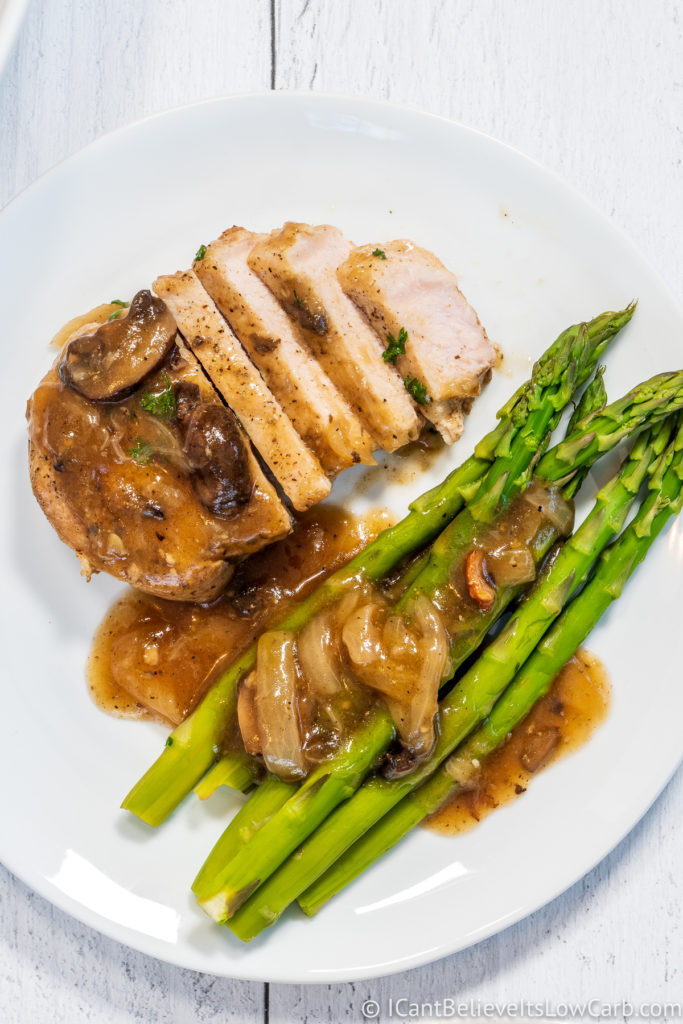 Instant Pot Pork Chops with asparagus on a white plate
