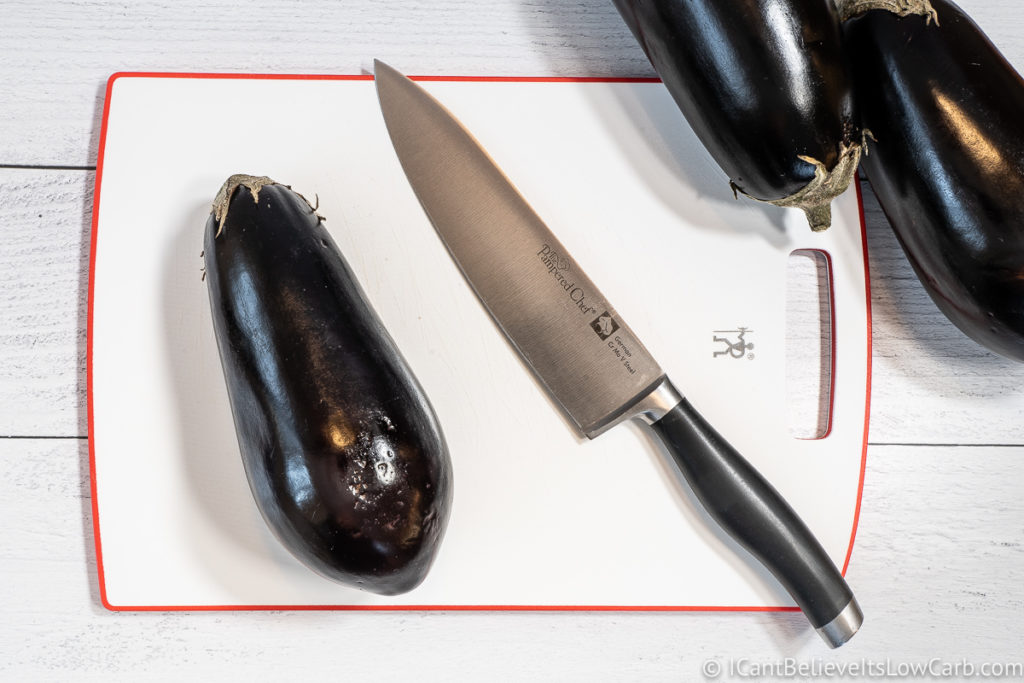 Eggplant on a cutting board with knife