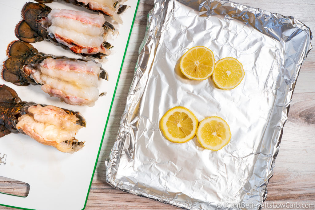 Lobster Tails on cutting board and sheet pan with lemon slices