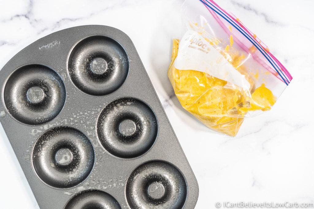 spraying donut pan with anti-stick spray