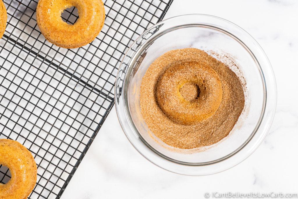 coating donuts in cinnamon sugar