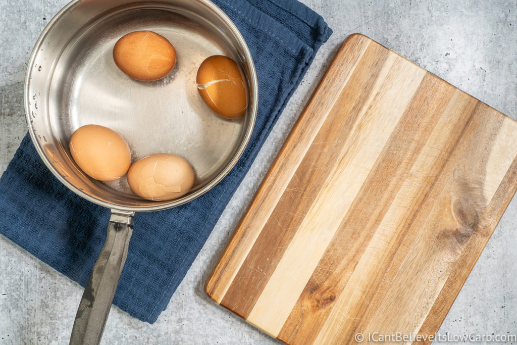 Soft Boiled Eggs in a pan in water and a cutting board