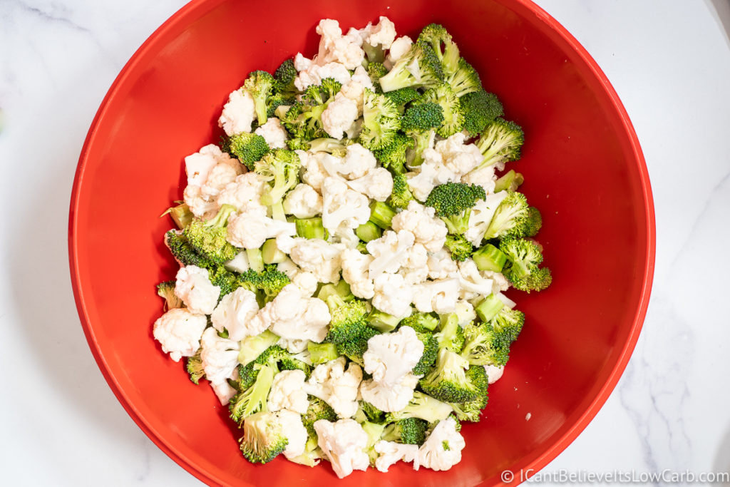 Mixing Broccoli and Cauliflower in a red bowl
