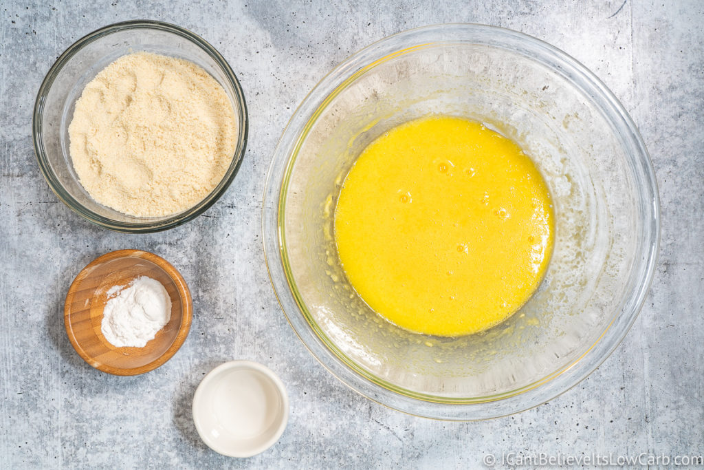 Bowl with egg butter mixture and bowls of almond flour and baking powder
